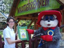 """Gabriele Koller von der Zwergensprache und Maskottchen Filippo vom Familypark Neusiedlersee mit dem neuen Babyzeichenschild """"Hase"""" vor dem Waldtierrennen"""